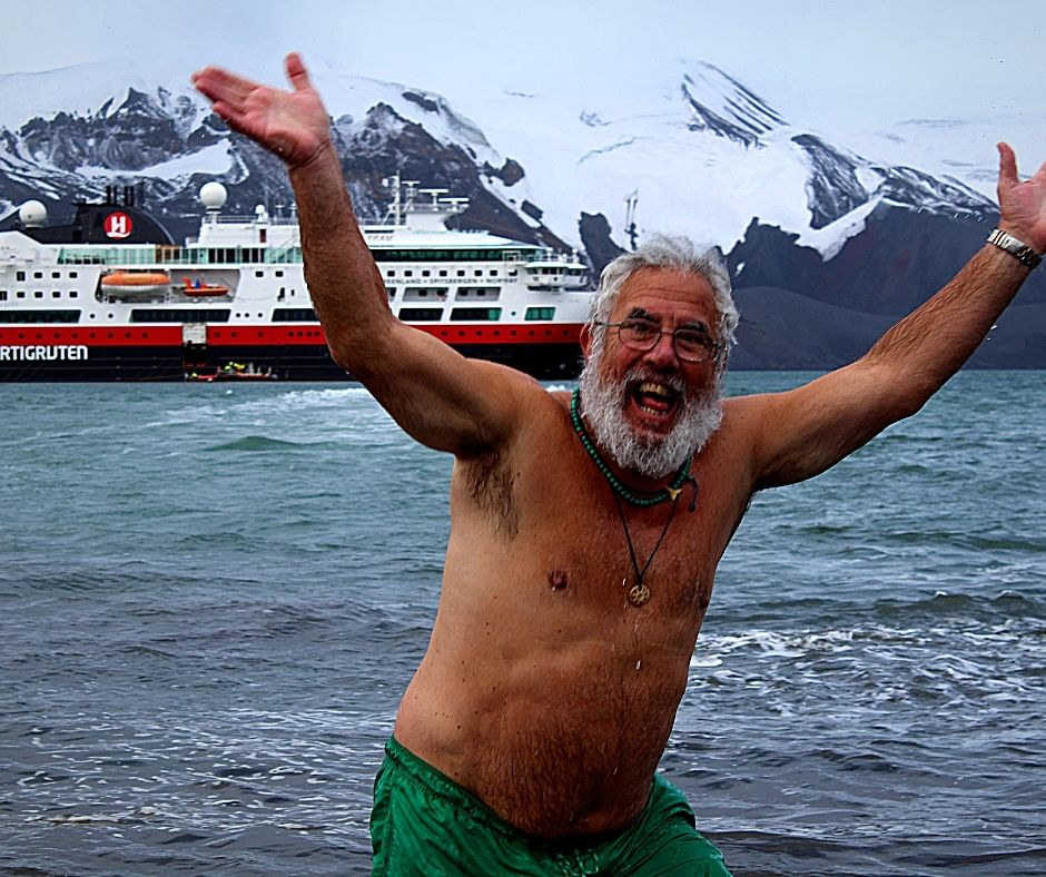 Man coming out of the water excitedly after doing a Polar Plunge in Antarctica