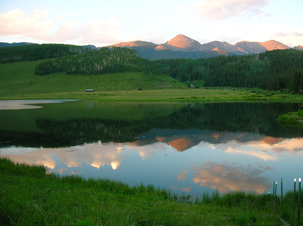 Mountains reflecting in the lake in Colorado. One epic long road trip in North America is through Colorado.